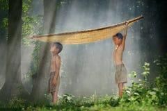 Due fratelli che fanno una pausa con una barca di bambù su una testa in T rurale Fotografia Stock