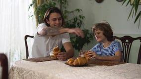 Due fratelli che si siedono in tavolo da cucina e che mangiano croissant con cappuccino Il fratello più anziano ha segnato la tes archivi video