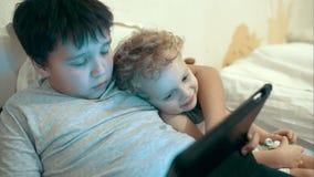 Due fratelli con il cuscinetto che si trova a letto intrattenimento archivi video