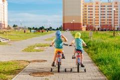 Due fratelli gemelli che guidano insieme le bici Immagine Stock