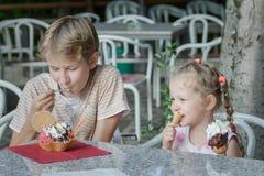 Due fratelli germani che mangiano dessert in gelateria italiano della barra di gelato fotografie stock libere da diritti