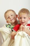 Due fratelli germani dei ragazzini che giocano con gli asciugamani Fotografia Stock