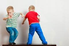 Due fratelli germani dei ragazzini che giocano insieme sulla tavola Fotografia Stock