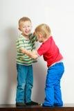 Due fratelli germani dei ragazzini che giocano insieme sulla tavola Fotografie Stock Libere da Diritti