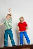 Due fratelli germani dei ragazzini che giocano insieme sulla tavola Immagini Stock Libere da Diritti