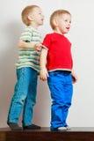 Due fratelli germani dei ragazzini che giocano insieme sulla tavola Immagini Stock