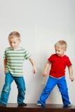 Due fratelli germani dei ragazzini che giocano insieme sulla tavola Fotografia Stock Libera da Diritti