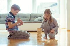 Due fratelli germani felici che giocano con i blocchi di legno a casa Fotografie Stock Libere da Diritti
