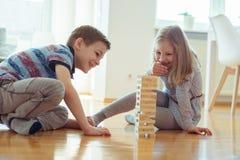 Due fratelli germani felici che giocano con i blocchi di legno a casa Immagine Stock