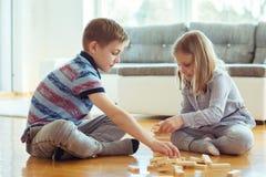 Due fratelli germani felici che giocano con i blocchi di legno a casa Immagini Stock Libere da Diritti