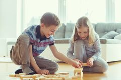 Due fratelli germani felici che giocano con i blocchi di legno a casa Immagini Stock