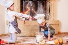 Due fratelli germani - ragazzo e ragazza - in cappelli del ` s del cuoco unico vicino al camino che si siede sul pavimento della  Immagine Stock Libera da Diritti