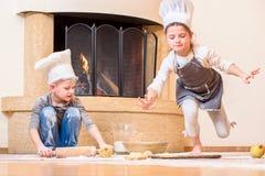 Due fratelli germani - ragazzo e ragazza - in cappelli del ` s del cuoco unico vicino al camino che si siede sul pavimento della  Fotografia Stock