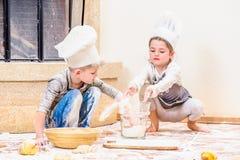 Due fratelli germani - ragazzo e ragazza - in cappelli del ` s del cuoco unico vicino al camino che si siede sul pavimento della  Fotografia Stock Libera da Diritti