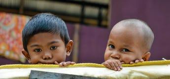Due fratelli piccoli poveri che esaminano macchina fotografica fotografia stock