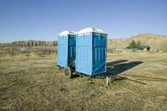 due fuori case bagni blu mobili si siedono sul rimorchio in mezzo ad un