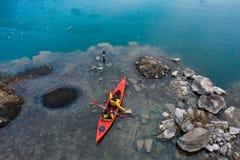 Due galleggianti atletici dell'uomo su una barca rossa in fiume fotografia stock libera da diritti