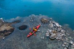 Due galleggianti atletici dell'uomo su una barca rossa in fiume fotografia stock