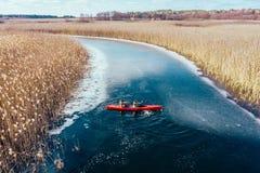 Due galleggianti atletici dell'uomo su una barca rossa in fiume immagini stock libere da diritti