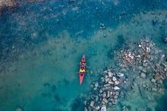 Due galleggianti atletici dell'uomo su una barca rossa in fiume fotografie stock libere da diritti