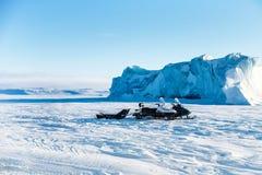 Due gatti delle nevi vicino ad un iceberg nel mare Glaciale Artico immagine stock