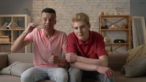 Due gay stanno sedendo sullo strato e la TV di sorveglianza, l'emozione di attesa e la delusione, tristezza, gridante LGBT video d archivio