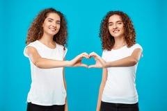 Due gemelli delle ragazze che mostrano il cuore con consegna il fondo blu Immagine Stock Libera da Diritti