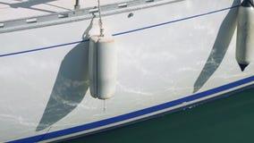 Due generi di cuscino ammortizzatore che haning giù dal bordo dell'yacht stock footage