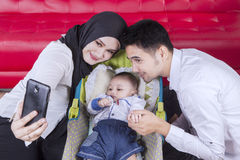Due genitori ed il loro bambino che prendono selfie fotografia stock libera da diritti