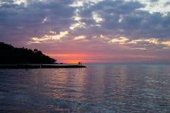 Due genti ad un pilastro nel tramonto sull'isola tropicale in Tailandia Fotografia Stock