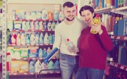 Due genti adulte sorridenti che selezionano i detersivi nel deposito Immagini Stock