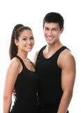 Due genti allegre nell'abbraccio nero degli abiti sportivi Fotografia Stock