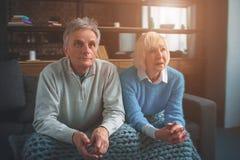 Due genti anziane stanno sedendo insieme Hanno messo il loro consegnano la t immagine stock