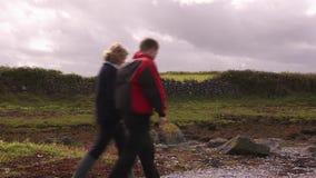 Due genti camminano dopo una vecchia parete di pietra in Irlanda stock footage