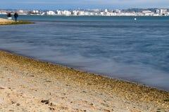 Due genti che camminano lungo la spiaggia con la città sull'orizzonte Fotografie Stock Libere da Diritti