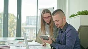 Due genti che discutono le idee facendo uso della compressa di Digital archivi video