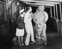Due genti che esaminano nella scossa un operatore subacqueo in un vestito degli operatori subacquei (tutte le persone rappresenta Fotografie Stock