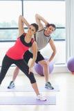 Due genti che fanno la forma fisica di potere si esercitano alla classe di yoga Immagini Stock