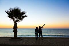 Due genti che godono della vista del mare dell'alba al lungonmare passeggiano Fotografia Stock
