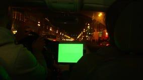 Due genti che guidano nell'automobile moderna e discutono l'itinerario in compressa con lo schermo verde video d archivio