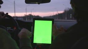 Due genti che guidano nell'automobile moderna e discutono l'itinerario in compressa con lo schermo verde archivi video