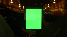 Due genti che guidano nell'automobile moderna e discutono l'itinerario in compressa con lo schermo verde stock footage