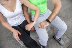 Due genti che per mezzo dell'orologio astuto di sport all'allenamento Fotografie Stock Libere da Diritti