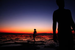Due genti che stanno sulla spiaggia con il tramonto variopinto stupefacente su fondo Immagini Stock Libere da Diritti