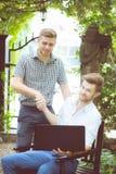 Due genti di affari americane di lavoro del successo felice della stretta di mano e del computer portatile fotografia stock