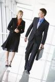 Due genti di affari che camminano nella conversazione del corridoio Immagini Stock Libere da Diritti