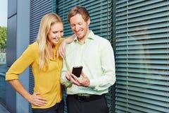 Due genti di affari che esaminano smartphone Immagine Stock Libera da Diritti