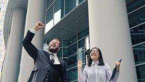 Due genti di affari che godono dei loro risultati archivi video