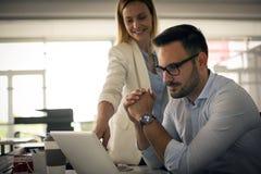 Due genti di affari che guardano qualcosa sul computer portatile Donna di affari - 2 Immagine Stock