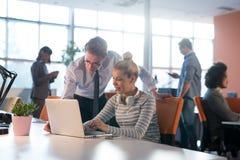 Due genti di affari che lavorano con il computer portatile in ufficio fotografia stock libera da diritti